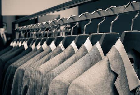 traje: Trajes de hombre colgando en una tienda de ropa.