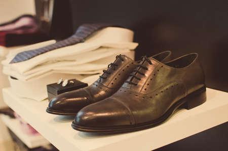 ropa colgada: Zapatos, camisetas y otras prendas de vestir en una tienda de moda de los hombres.