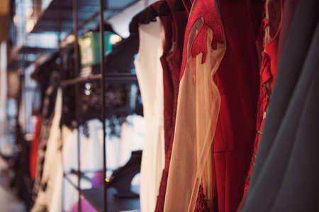 ropa colgada: Las mujeres la ropa en una tienda al por menor. Moda y concepto de las compras. Foto de archivo