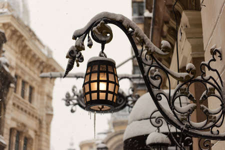bucuresti: Fancy lantern covered with snow in a winter day - urban concept.