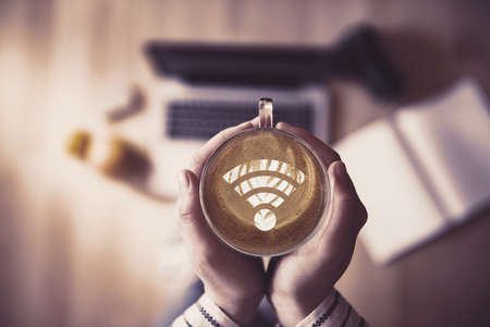 Girl holding a cup of coffee with wi-fi symbol.