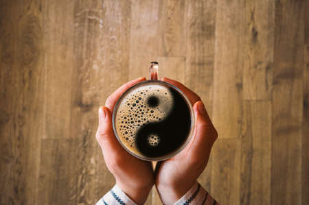 Girl holding a coffee cup with ying and yang symbol. Stock Photo