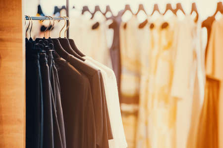 Bunte Kleidung auf Kleiderbügeln in einem Luxus-Modegeschäft mit Hintergrundbeleuchtung Effekt. Standard-Bild - 71583423