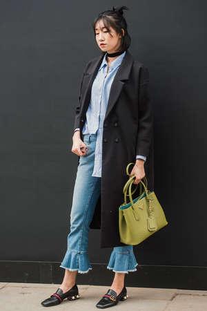 London, England – February 18, 2017: Stylish girl wearing Prada handbag and Gucci shoes, outside the London Fashion Week show. Editorial