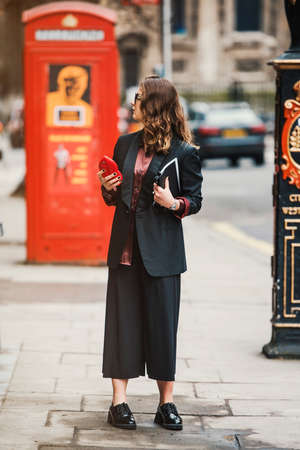 London, England – February 19, 2017: Girl wearing a fashionable outfit outside the location of London Fashion Week.
