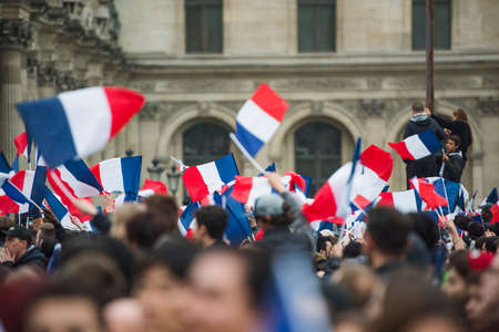 Paris, France - May 7, 2017: People waving french flags in Paris after presidential elections.