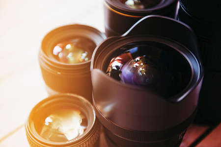 shutter aperture: Professional camera lenses on a wood background.