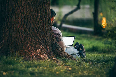 Working in nature - man with a laptop in a park