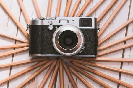 Creative photography concept - vintage camera surrounded with colored pencils.