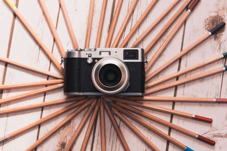 old notebook: Creative photography concept - vintage camera surrounded with colored pencils.