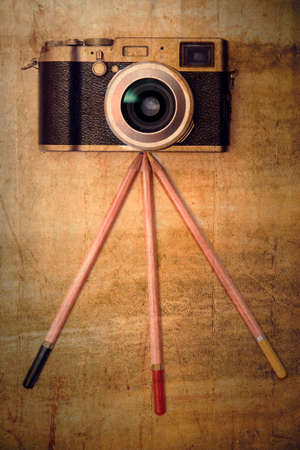 old notebook: Creative photography concept - vintage camera on a pencil tripod.