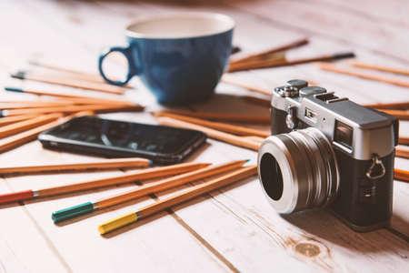 Concetto di luogo di lavoro creativo: caffè, smart phone e fotocamera su uno sfondo di legno. Archivio Fotografico - 79191653