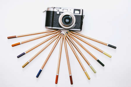 Creative photography concept - vintage camera on a pencil tripod.