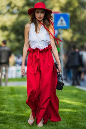 Milan, Italy - September 22, 2017: Sexy girl with fashionable look, dressed with a red skirt and a white shirt outside Armani Fashion Show at Milan Fashion Week - street style concept.