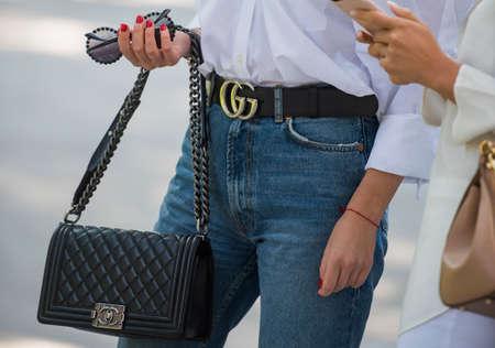 Milan, Italy - September 22, 2017: Fashionista with Gucci handbag outside a fashion show during Milan Fashion Week.