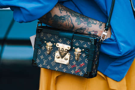 Milan, Italy - September 22, 2017: Tatoo girl with a stylish outfit wearing a Louis Vouitton luxuty handbag.