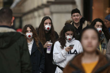 Milan, Italy - February 23, 2020: Coronavirus emergency in Milan, citizens and tourists stroll through the city center wearing protective masks.