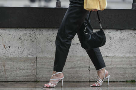 Paris, France – March 2, 2020: Woman wearing black leather trousers, white high heel sandals and a black Prada handbag - streetstylefw20 Editorial