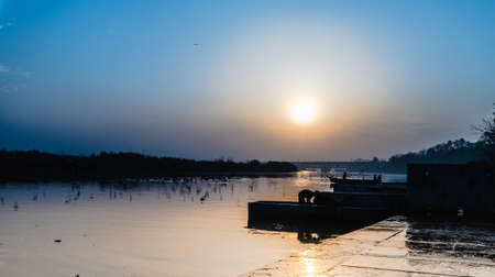 boatman: Sun rising at Yamuna Ghat, Delhi where few people working at their boat iappearing in Silhouttle