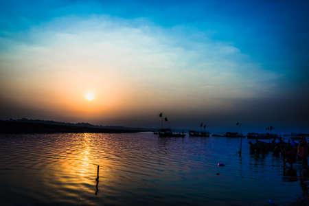morning blue hour: Pilgrims taking a holy bath at Sangam during sunrise at Prayag, Allahabad, UP