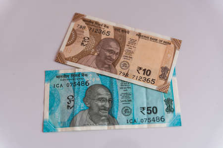 Indian currency notes of Rupees Fifty and Rupees Ten on white background