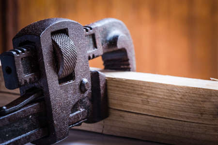 Conept shot of stained pipe wrench hand tool calmped a wooden peice in isolated background