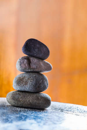 Four Pebble Stones stacked on bright surface with dark background
