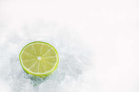 Juicy lemon in ice cubes background. Lemon and mint with crushed ice / ices cubes. Lemon ring. Ice background. Healty 2020.