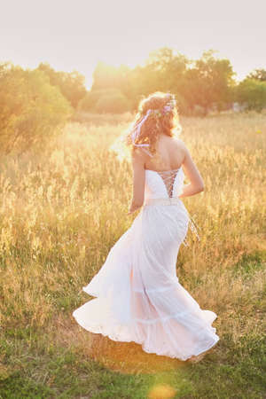 Young girl in a white dress in the meadow. Woman in a beautiful long dress posing in the garden. Stock Photo