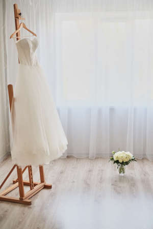 Beautiful wedding dress on a hanger in the room light background