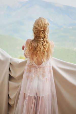 silhouette de jeune mariée belle fille dans un peignoir se dresse sur le balcon donnant sur les montagnes y et attendant le marié