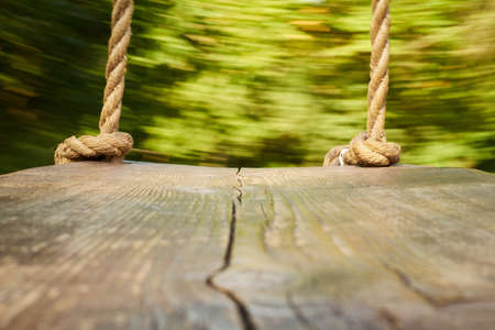 wooden swing with thick ropes. the camera is on the swing