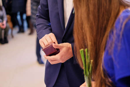 A man in a blue suit holds a small wooden gift box of wedding rings. wedding gift