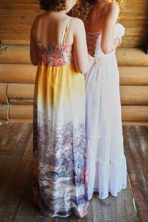 the bride is fastening a wedding dress.bridesmaid helps the bride .girlfriend helps bride Foto de archivo