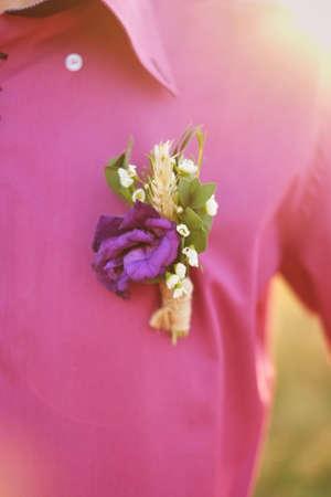 Groom's boutonniere on a purple shirt