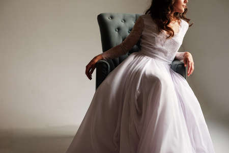 Young bride in a magnificent dress in the studio sits in an easy chair