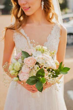 Mariée tenant un bouquet de mariage dans des couleurs rose pastel. Banque d'images