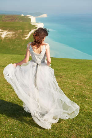 Wedding. Wedding by the sea. A young bride walks away along a cliff by the sea. Seven Sister England. Stockfoto