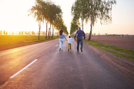Happy family dad mom and son playing outdoors on the road near the field, watching the beautiful emotional sunset in the backlight Reklamní fotografie