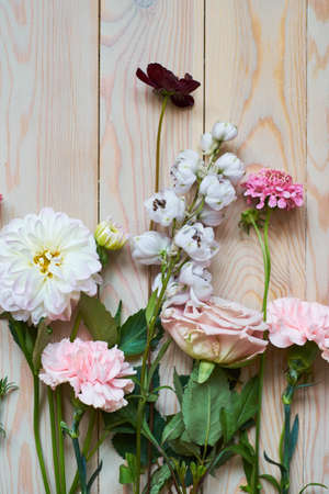 flowers on rustic wooden planks background flat lay