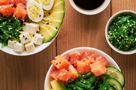 Raw Organic Poke Bowl with with rice, avocado, salmon, mango, cucumbers, chuka salad, quail eggs sweet onions two plates close-up on wooden background top view