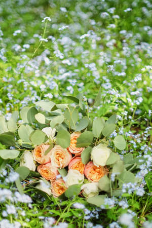 Beautiful wedding bouquet is lying in the grass. Engagement rings are on the flowers. Orange colours of fall and autumn in floral composition.