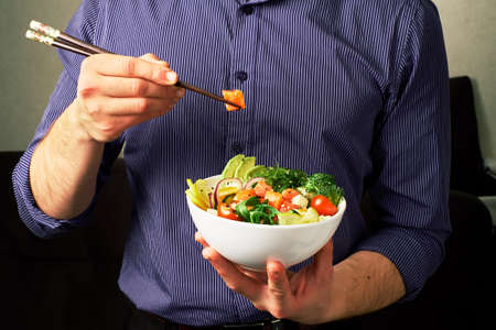 man in a shirt holds poke bowl with salmon, avocado, cucumbers, arugula, broccoli, rice, carrots, and chuha with chopsticks