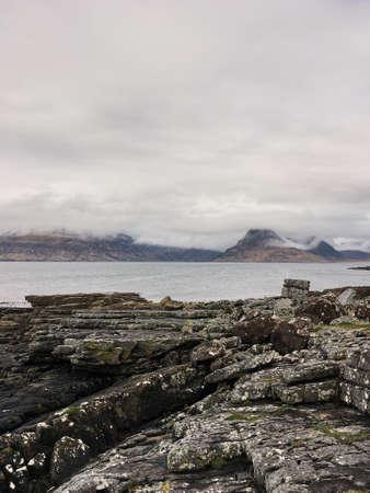 Rocky coast, cloudy mountain peaks, Scotland, Isle of Skye, early spring