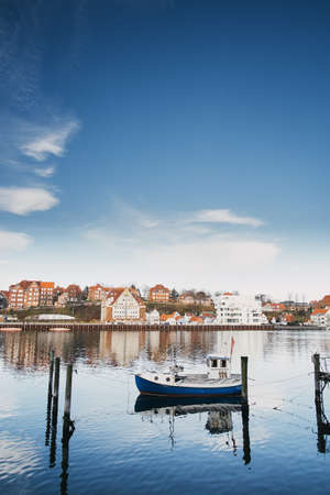 Sonderborg, Denmark - April 9, 2015: A small white fishing boat on the background of an old European town Reklamní fotografie