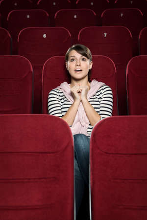 Emotional girl watching a movie with hope Stock Photo - 13627939