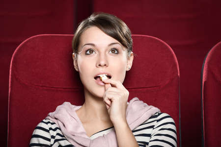 sits on a chair: Woman watching a movie with enthusiasm
