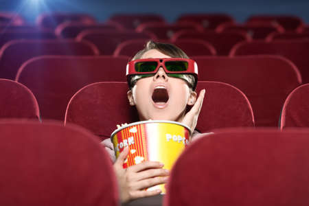 Shoked young woman with popcorn in 3D movie photo