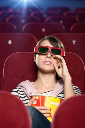 theater popcorn: Young woman wipes tears watching a movie at the cinema Stock Photo