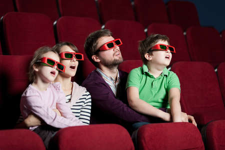 family movies: Frightened family watching a 3D movie Stock Photo
